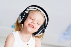 Pretty girl listening to music on headphones Stock Image