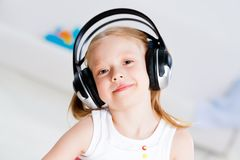Pretty girl listening to music on headphones Stock Images