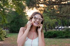 Pretty girl is listening to music in headphones outside. Favourite song. Woman is having rest in the park.  royalty free stock photo