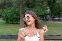 Pretty girl is listening to music in headphones outside. Favourite song. Woman is having rest in the park.  royalty free stock images