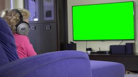 Pretty girl listening to music with headphones and watching tv. Green screen. stock footage