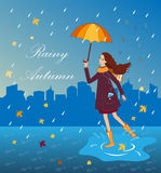 Pretty girl listening to music with an umbrella. Happy woman on the city background Royalty Free Stock Images