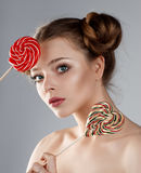 Pretty girl with lollipops. Young girl with lovely hairdo posing with lollipops. Studio shooting. Beauty shooting Royalty Free Stock Photography
