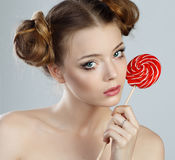 Pretty girl with lollipops. Young girl with lovely hairdo posing with lollipops. Studio shooting. Beauty shooting Royalty Free Stock Images
