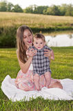 Pretty girl sitting on blanket holding baby. Blonde long haired Girl holding baby boy up with feet touching quilt outdoors Royalty Free Stock Images