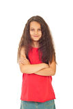 Pretty girl with long curly hair. Pretty girl seven years old with long curly hair standing with arms folded isolated on white background Royalty Free Stock Photo