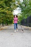 Beautiful brunette girl walking with dog in the park. Animal concept. Pretty girl with long hair having fun with doggie mops in the park outdoors. Young woman Royalty Free Stock Image