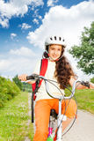 Pretty girl with long hair in helmet rides a bike Stock Photos