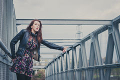 Pretty girl with long hair hitchhiking on a bridge Royalty Free Stock Photography