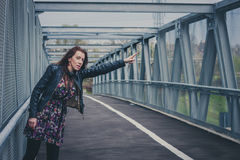Pretty girl with long hair hitchhiking on a bridge Royalty Free Stock Images