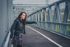 Pretty girl with long hair hitchhiking on a bridge Royalty Free Stock Image