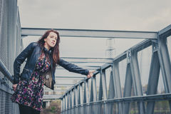 Pretty girl with long hair hitchhiking on a bridge Royalty Free Stock Photos