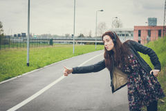Pretty girl with long hair hitchhiking in the street Stock Image