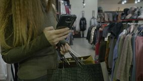 Pretty girl with long hair holding shopping bags in a store mall and uses her smartphone to text her friends -. Pretty girl with long hair holding shopping bags stock video footage