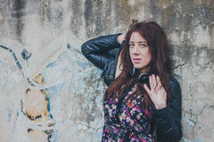 Pretty girl with long hair leaning against a concrete wall Royalty Free Stock Photos