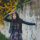 Pretty girl with long hair leaning against a concrete wall Royalty Free Stock Photo