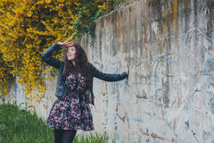 Pretty girl with long hair leaning against a concrete wall Royalty Free Stock Image