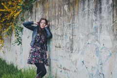 Pretty girl with long hair leaning against a concrete wall Stock Photography