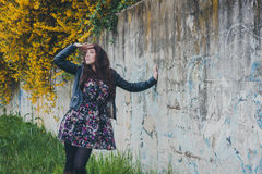 Pretty girl with long hair leaning against a concrete wall Royalty Free Stock Photography