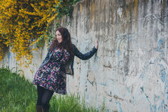 Pretty girl with long hair leaning against a concrete wall Stock Images