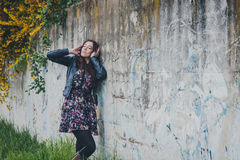 Pretty girl with long hair leaning against a concrete wall Royalty Free Stock Images