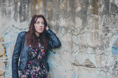 Pretty girl with long hair leaning against a concrete wall Stock Photo