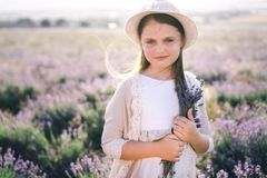 Pretty girl with long hair in a linen dress and a hat with a bouquet of lavender standing in a lavender field. royalty free stock photo