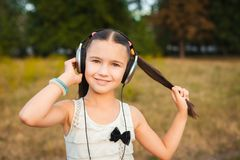 Pretty girl with long hair listening song. Pretty girl with long hair having nice rest outdoor, beautiful girl with black and silver headphone listening song on Royalty Free Stock Photo