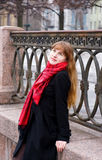 Pretty girl with long hair in the red scarf. Pretty young girl with long hair in the red scarf and black coat Royalty Free Stock Photos