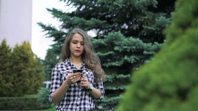 Pretty girl with long hair using phone by trees background stock video footage