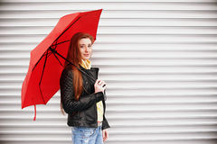 A pretty girl with long red hair, in a black leather jacket with a red umbrella in her hands, walks and smiles Portrait in the ope royalty free stock image