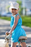 Pretty girl looking back from shoulders when riding bicycle Stock Photos