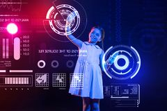 Pretty girl looking happy while dealing with a futuristic device royalty free stock photos