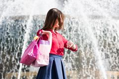 Pretty girl is looking at her watch. Fountain background. Royalty Free Stock Photography