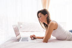Pretty girl looking at laptop monitor while lying on bed. In her room royalty free stock photos