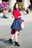 Pretty girl looking like a celebrity is shopping. Blue and red clothing with back shoes. Urban background Stock Photo