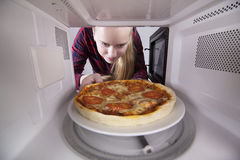 Pretty girl looking in microwave is holding plate with pizza Stock Image