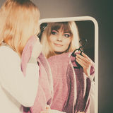 Pretty girl looking into mirror. Pretty happy woman watching at her into mirror in clothing from new collection wardrobe. Young undecided shopper girl choosing Stock Photo