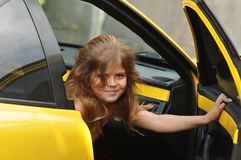 Pretty girl looking out from yellow sport car Stock Image