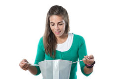 Pretty girl looking in a silvered bag shopping. On a over white background royalty free stock images