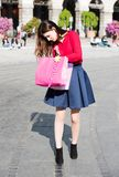 Pretty girl is looking for something in her bags. Pretty girl looking like a celebrity is shopping. Blue and red clothing with back shoes. Urban background Royalty Free Stock Photo