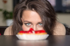 Pretty girl Looking to strawberry cake Royalty Free Stock Image