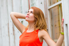 Pretty girl looking up standing near wall Royalty Free Stock Photos