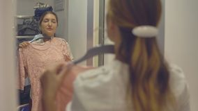 Pretty girl looks at her reflection in the mirror while trying on clothes in fashion store while shopping. Pretty girl looks at her reflection in the mirror stock footage