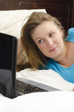 Pretty girl looks at laptop Stock Images