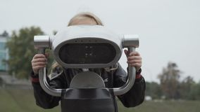 Pretty girl looks into telescope in the park stock video