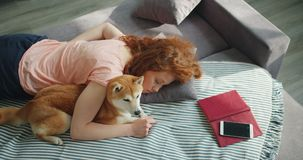 Pretty girl and loyal dog sleeping together on sofa at home relaxing during day. Pretty girl and her loyal dog are sleeping together on sofa at home relaxing stock footage