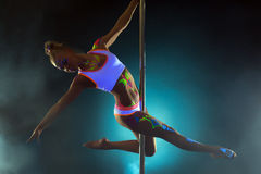 Pretty girl with luminous makeup dancing on pole Stock Image