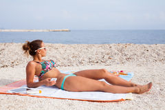 Pretty girl lying on the beach and sunbathing with phone in her Royalty Free Stock Photography