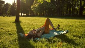 Pretty girl lying down on a meadow and talking by smartphone. Female flip over from belly to back. stock video footage